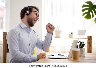 Happy businessman wearing headphones singing song at workplace, funny employee or freelancer using laptop, enjoying favorite track, listening to music, dancing, having fun during break