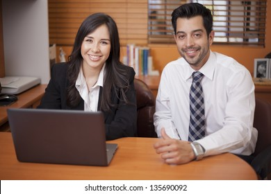Happy businessman and woman doing some work together at the office