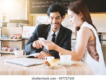Happy businessman and woman have a meeting and looking at smart phone in modern cafe. Selective focus.