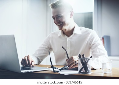 Happy businessman working at his office with laptop. Young smiling man sitting at his workplace with notebook computer and holding glasses in hand