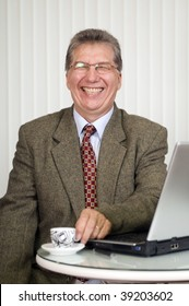 Happy businessman, working with laptop in the office