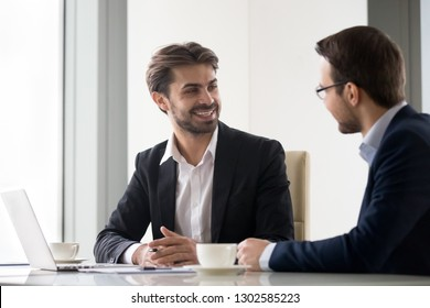 Happy businessmen partners executives talking at work enjoy teamwork discussing new ideas, smiling manager and client having friendly conversation cooperation at business office meeting with laptop