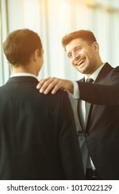 The happy businessmen pat on the shoulder