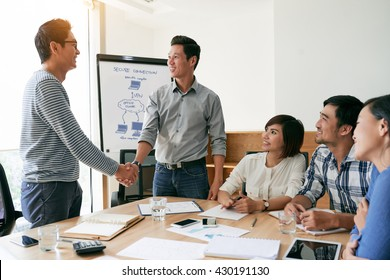 Happy businessmen shaking hands after successful meeting