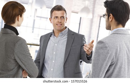 Happy businesspeople discussing at office.