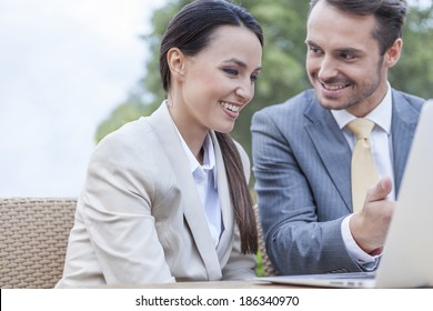 Happy businesspeople discussing over laptop outdoors