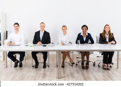 Happy Businesspeople Sitting At Conference With Graph On Desk