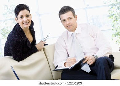Happy businesspeople sitting of couch at office and  teamworking, they looking up to camera and smiling.