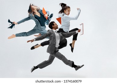 Happy businesswoman and african man dancing in motion isolated on white studio background. Flexibility and grace in business. Human emotions concept. Office, success, professional, happiness