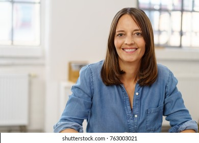 Happy businesswoman with a beaming friendly warm smile sitting at a desk in the office in a close up portrait