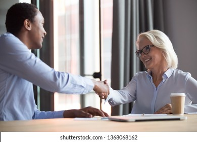 Happy businesswoman broker insurer hr manager handshake african businessman client customer hire candidate make business deal for legal services, insurance purchase, take bank loan at office meeting