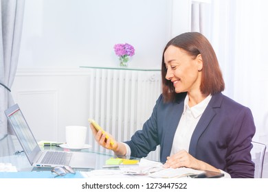 Happy businesswoman doing paperwork in the office