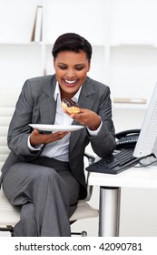 Happy businesswoman eating in the office. Business concept.