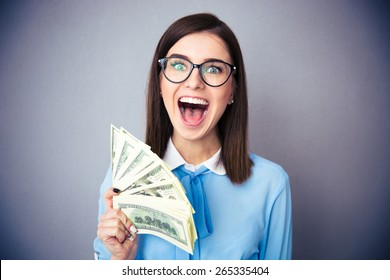 Happy businesswoman holding bill of dollars and screaming over gray background. Wearing in blue shirt and glasses. Looking at camera