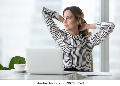 Happy businesswoman holding hands behind head finished work at workplace thinking dreaming of vacation, satisfied dreamy female worker taking break to rest feeling no stress free enjoying wellbeing