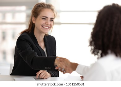 Happy businesswoman hr manager handshake hire candidate selling insurance services making good first impression, diverse broker and client customer shake hand at business office meeting job interview