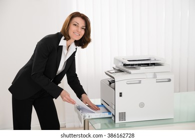 Happy Businesswoman Inserting Papers In Photocopy Machine At Office