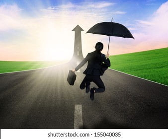 Happy businesswoman jumping with umbrella on the road