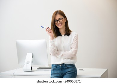 Happy businesswoman leaning on the table in office