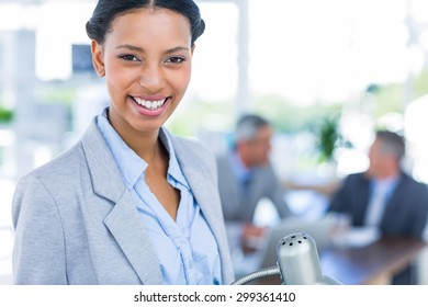 Happy businesswoman looking at camera with her colleagues behind her in office