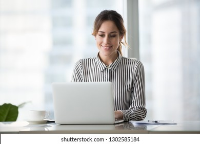 Happy businesswoman professional worker working online doing job on laptop at desk, smiling female employee executive typing message using corporate computer software for business in modern office
