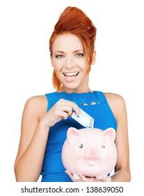 happy businesswoman putting cash money into piggy bank