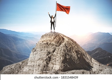 Happy businesswoman with red flag standing on mountain top. Success and startup concept.  Leadership and victory concept