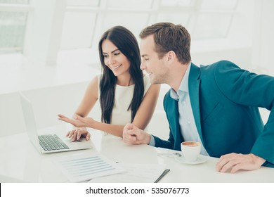 Happy businesswoman showing  financial report on her laptop to colleague