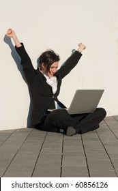 Happy businesswoman  sitting with a laptop at the wall outdoors