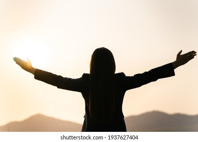 Happy businesswoman spreading arms and watching the mountain silhouette. Business success concept, freedom emotions