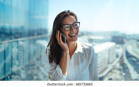 Happy businesswoman standing in her office in a highrise building overlooking the cityscape. Businesswoman talking on mobile phone standing near window in office.