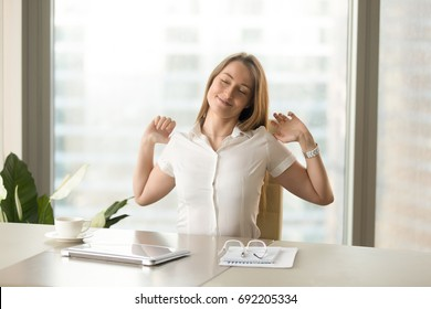 Happy businesswoman stretching arms at workplace, smiling woman enjoying pleasant working day start, satisfied office worker feeling fresh after good morning coffee, finished completed work done