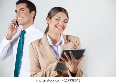 Happy businesswoman with tablet computer and manager with smartphone in the background