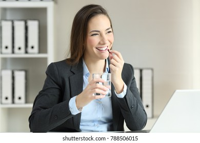 Happy businesswoman taking a pill working at office