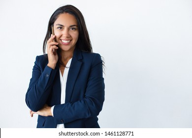 Happy businesswoman talking by smartphone. Attractive young woman in formal wear talking by cell phone and smiling at camera isolated on grey background. Connection concept