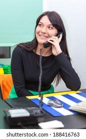 Happy businesswoman talking on  telephone in office