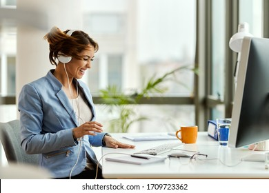 Happy businesswoman tossing her hair while listening music over headphones and working in the office.