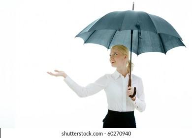 Happy businesswoman under open umbrella stretching her arm