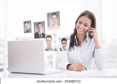 Happy businesswoman using laptop at her desk against profile pictures