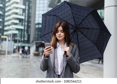 Happy businesswoman using mobile phone near office, young girl browsing phone smiling under umbrella while it is raining outdoors, female manager texting smartphone near modern bank building