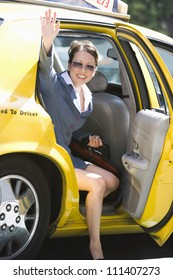 Happy businesswoman waving hand while sitting in taxi
