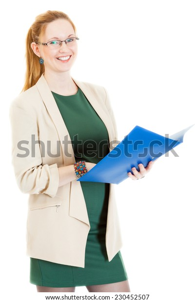 happy businesswoman wearing a green dress and jacket stands with folder