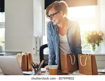 Happy businesswoman working in a home office standing looking at her laptop computer surrounded by gift bags and packaging for the products for sale on her new website