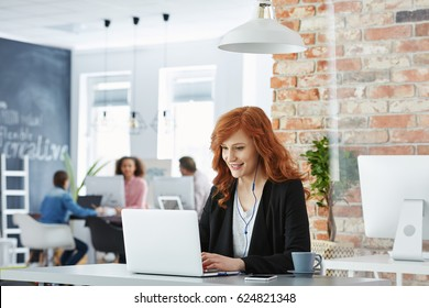 Happy businesswoman working in modern office with laptop