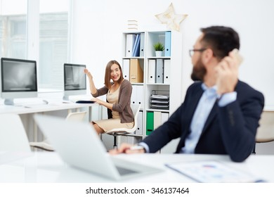 Happy businesswoman at workplace looking at her boss in office