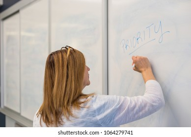 happy businesswoman writing on whiteboard in meeting