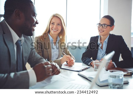 Happy businesswomen listening to young man explanations