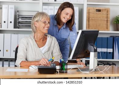 Happy businesswomen using computer at desk in office