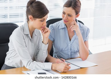 Happy businesswomen working together at desk in office