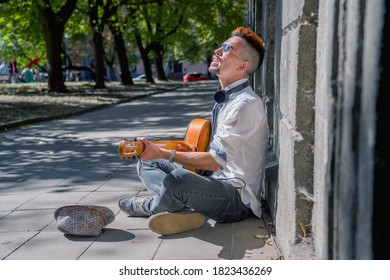 Happy busker street musician sitting on a city sidewalk and playing music with guitar. Freedom, music and art concept.